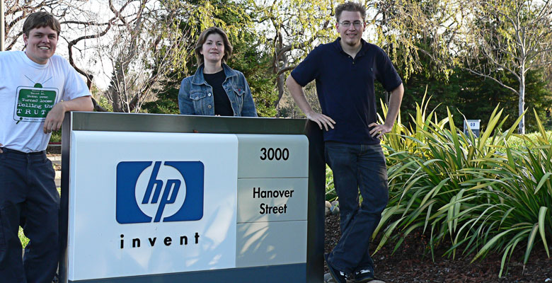 Daniel, Zhanna and Tim behind the HP company logo