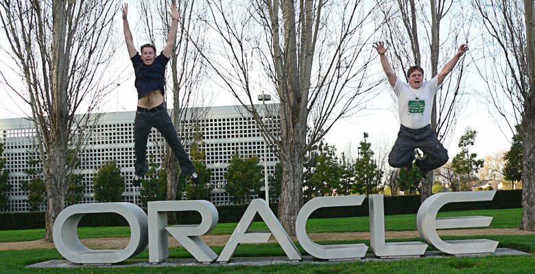 Tim and Daniel jumping of the Oracle sign